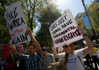 Protesters hold up posters as they take part in the Women's March outside the U.S. embassy, in Mexico City