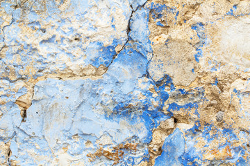 Old stone rustic cracked wall painted in blue paint as decay texture background