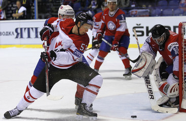 Skinner of Canada attacks against Norway's Haugen during their qualification round game at the Ice Hockey World Championships in Kosice