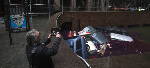 A man uses an iPad to photograph submerged vehicles in a parking structure in the financial district of Lower Manhattan, New York