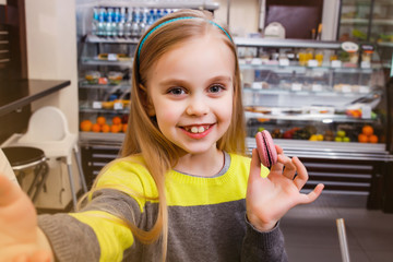 A little girl stands near a showcase with macaroon and makes selfie