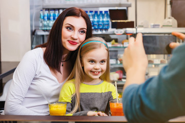 A man makes picture of young mother with her little dauther at a table in a cafe