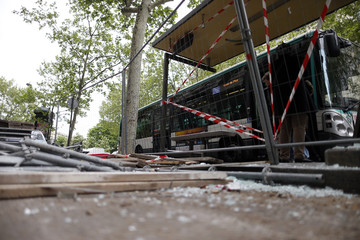 Broken glass and debris from a bus stop cover the sidewalk in Paris the day after clashes between troublemakers and police