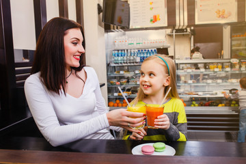 young mother with her little dauther sitting at a table in a cafe and drinking juice
