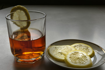 Whiskey in a crystal glass and a lemon on a porcelain dish