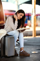 Girl on train station with luggage reading a book