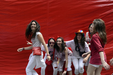 Revellers pose in front of a red tarpaulin during the start of the San Fermin Festival in Pamplona