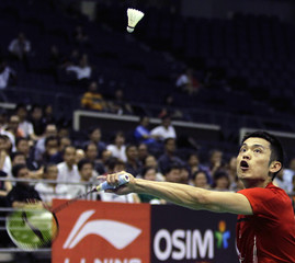 China's Lin returns a shot to Indonesia's Santoso in their men's singles quarter-finals match at the Singapore Badminton Open tournament