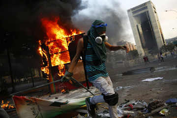 An anti-government protester sets up a barricade next to a burning kiosk during a protest at Altamira square in Caracas