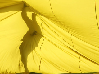 A crew member is silhouetted behind a hot-air balloon as it is being inflated during sunrise in Luxor