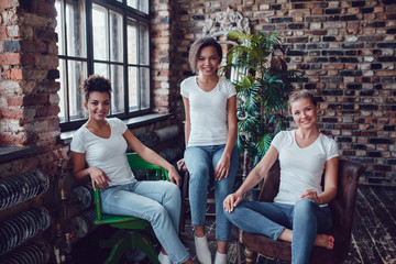 Three attractive girls in white T-shirts are sitting on armchairs near the window.