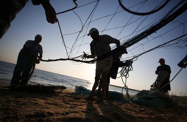 Fishermen prepare their net before casting it into the sea along the Caparica coast in central Portugal