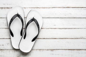 White Beach flip flop on white wooden floor