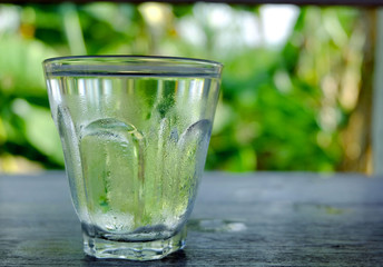 A glass of cold water on nature background.