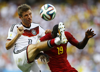 Germany's Mueller fights for the ball with Ghana's Mensah during their 2014 World Cup Group G soccer match at the Castelao arena in Fortaleza