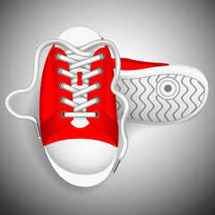 Red sneakers on a grey background.