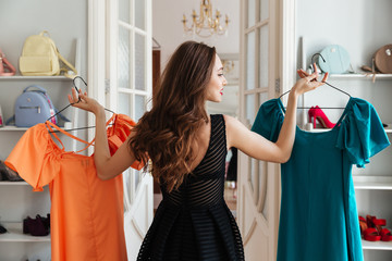 Young lady standing in clothes shop choosing dresses
