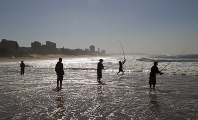 Fishermen attempt to catch the game fish which follow the sardine shoals during the annual sardine run at Warner Beach