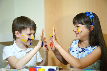 Joyful children with paints on their faces. Children paints faces with colors.