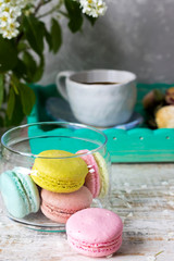 Different macaroons on a light wooden background and bird-cherry branches