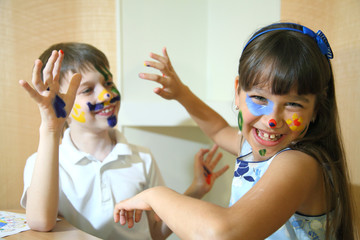 Joyful children with paints on their faces. Creativity and education concept.