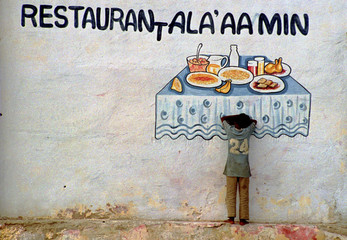 A starving Somali child leans against a wall in port Mogadishou
