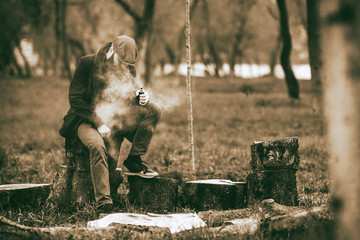 Vape man. Photo of a brutal bearded young man having rest after chop firewood and vaping an electronic cigarette in the village. Toned. Lifestyle.
