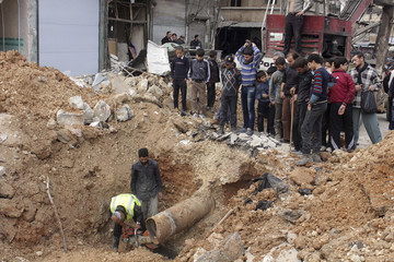 Workers try to fix damage after what activists said was shelling by forces loyal to Syria's President Bashar al-Assad in Aleppo
