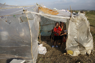 Survivors of Haiti's earthquake stand inside a makeshift tent at the Cite Soleil in Port-au-Prince