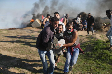 Palestinian protesters evacuate a local Palestinian photographer who was shot by Israeli troops during clashes near border between Israel and Central Gaza Strip