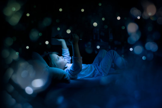 little child girl using tablet technology in bed by night at home. toughtful kid daughter in bedroom watching movie or reading or playing game. real people candid dark dreamy shot with light flares