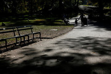 A girl is seen in silhouette walking with a woman during warm weather in Central Park in New York City