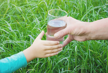Woman giving a glass of clean water to a child. Selective focus.