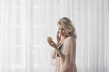 Pretty blonde Caucasian woman standing by the window and putting make up on her face.