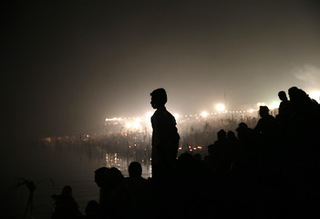 A man watches as Hindu devotees worship the Sun god Surya on the banks of the river Yamuna during the Hindu religious festival of Chatt Puja in New Delhi