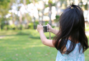 Child girl taking pictures on camera in the garden, Focus at camera.