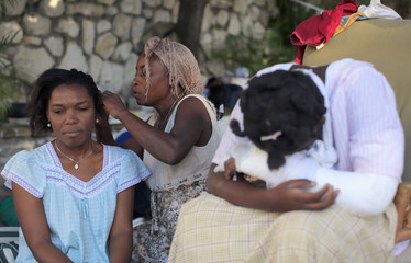 Earthquake survivors wait for aid in a makeshift refugee camp at the Petion ville neighborhood in Port-au-Prince