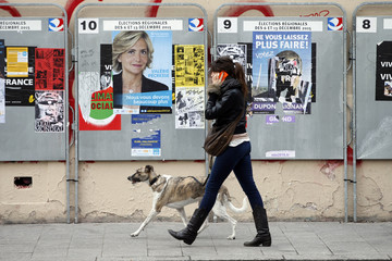 A woman walks her dog along campaign posters of candidates in Ile de France region which are glued on metallic electoral panels near a voting station ahead of the upcoming French regional elections in Paris