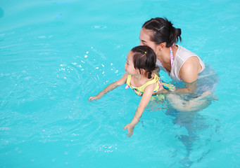 Close up mother teaching kid in swimming pool.