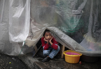 A boy takes shelter under plastic sheets in downtown Guatemala City