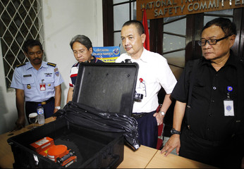 Indonesian officials stand near the cockpit voice recorder of AirAsia QZ8501 during news conference at the National Transportation Safety Committee office in Jakarta