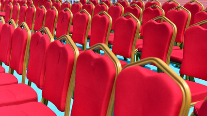 Traditional classically regal ornate rounded wood armed formal plush deep red velvet chairs in a stadium for a ceremony