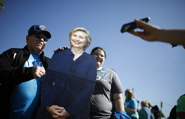 Supporters of former U.S. Secretary of State Hillary Clinton have their picture taken with a cardboard cutout of Clinton at the 37th Harkin Steak Fry in Indianola, Iowa