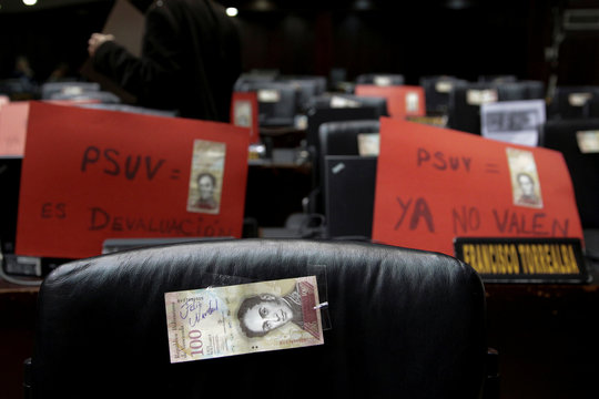 "A 100 bolivar note with ""Merry Christmas"" written on it and signs, are seen on the desks of lawmakers from PSUV, before a session of the National Assembly in Caracas"