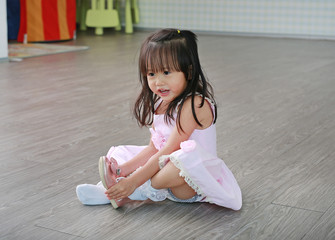 Cute little girl in pink dress sitting on floor tries to put on her shoes in the playroom.