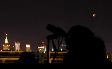 A woman star-gazes as the supermoon, appearing in a dim red colour, is pictured covered by the Earth's shadow during a total lunar eclipse above the city skyline in Warsaw