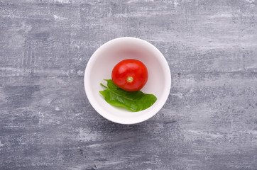 Spring greens for health.  Fresh sorrel  and tomato in plate on grey wooden table.