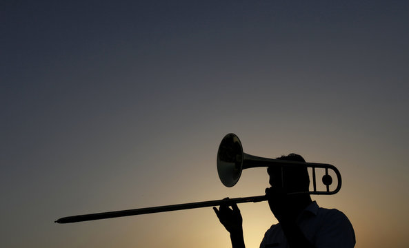 A Pakistani Navy soldier is silhouetted while playing a bugle during a national flower exhibition at Karachi's Clifton beach