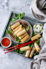 Fried spring rolls with red and white sauces, served in china plate on wood tray with fresh green salad and wooden chopsticks over gray blue texture background. Flat lay, space. Asian food