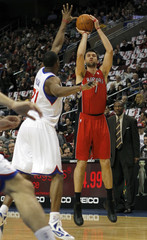 Raptors center Bargnani shoots under pressure from the 76ers forward Young during their NBA basketball game in Philadelphia